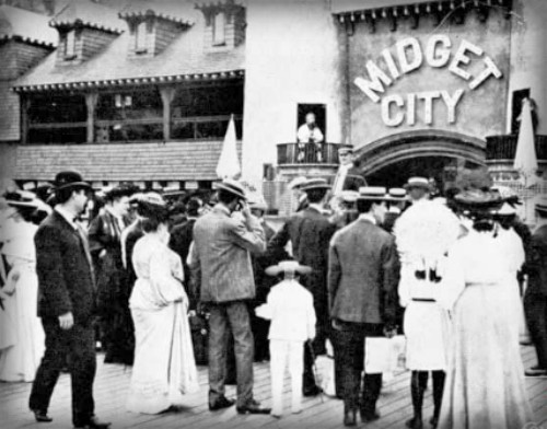 a crowd of people in Victorian Era clothing standing in front of Midget City. Image: Library of Congress.